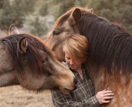 a picture of ren hurst, a white woman with short blonde hair standing in between two horses with brown fur