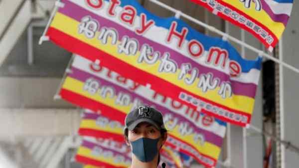 """En kvinde, der bærer en beskyttelsesmaske, går ned under bannerne, der læser """"Stay Home"""" i Tokyo, hvor undtagelsestilstanden vil forblive på plads på trods af at hun blev løftet i 39 andre præfekturer torsdag.   REUTERS"""