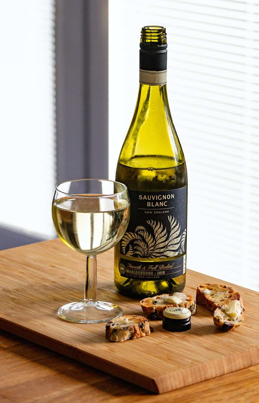 bottle of sauvignon blanc and glass with slices of cheese