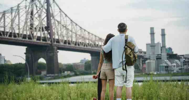 anonymous romantic couple standing near bridge and enjoying cityscape