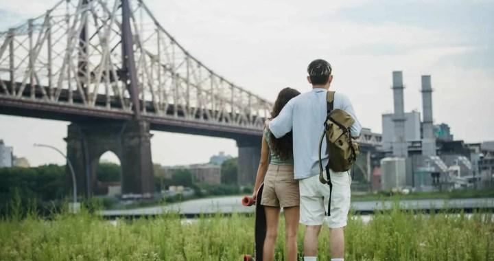 anonymous romantic couple standing near bridge and enjoying cityscape