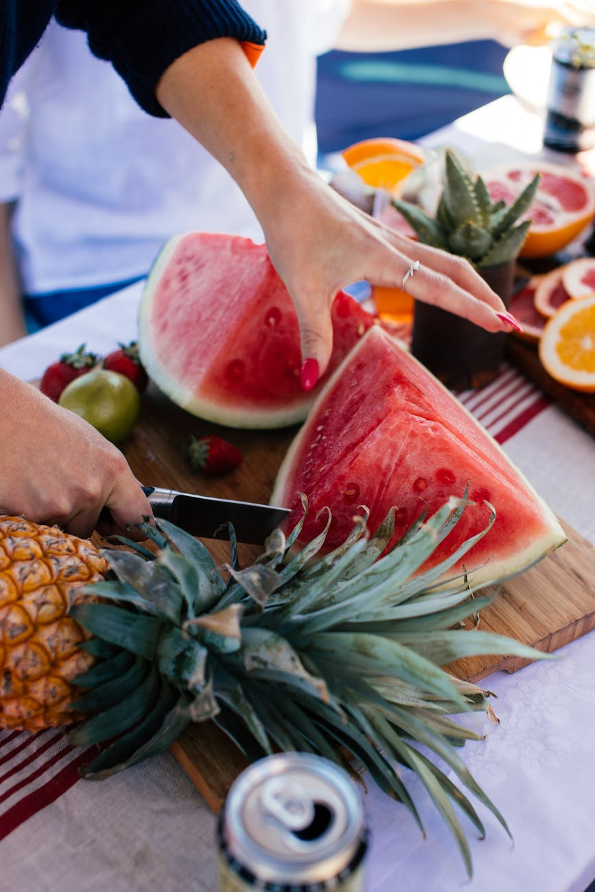 crop woman cutting watermelon with knife