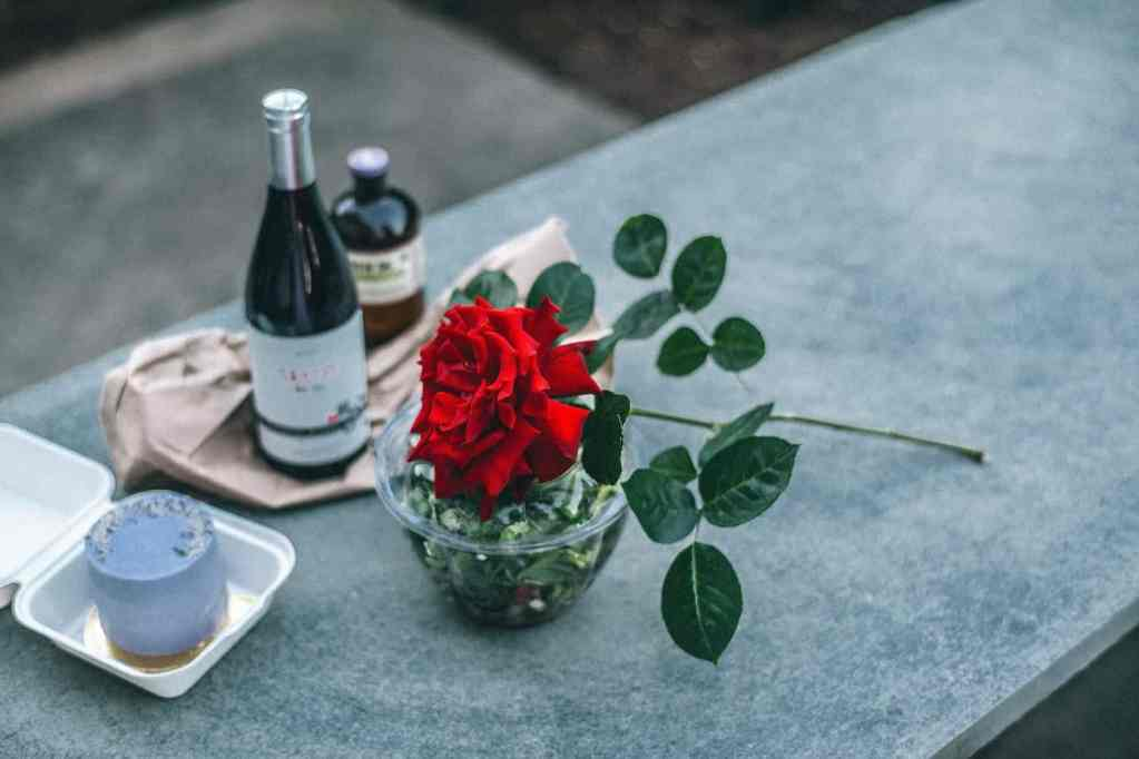 composition of red rose placed on parapet near champagne bottle