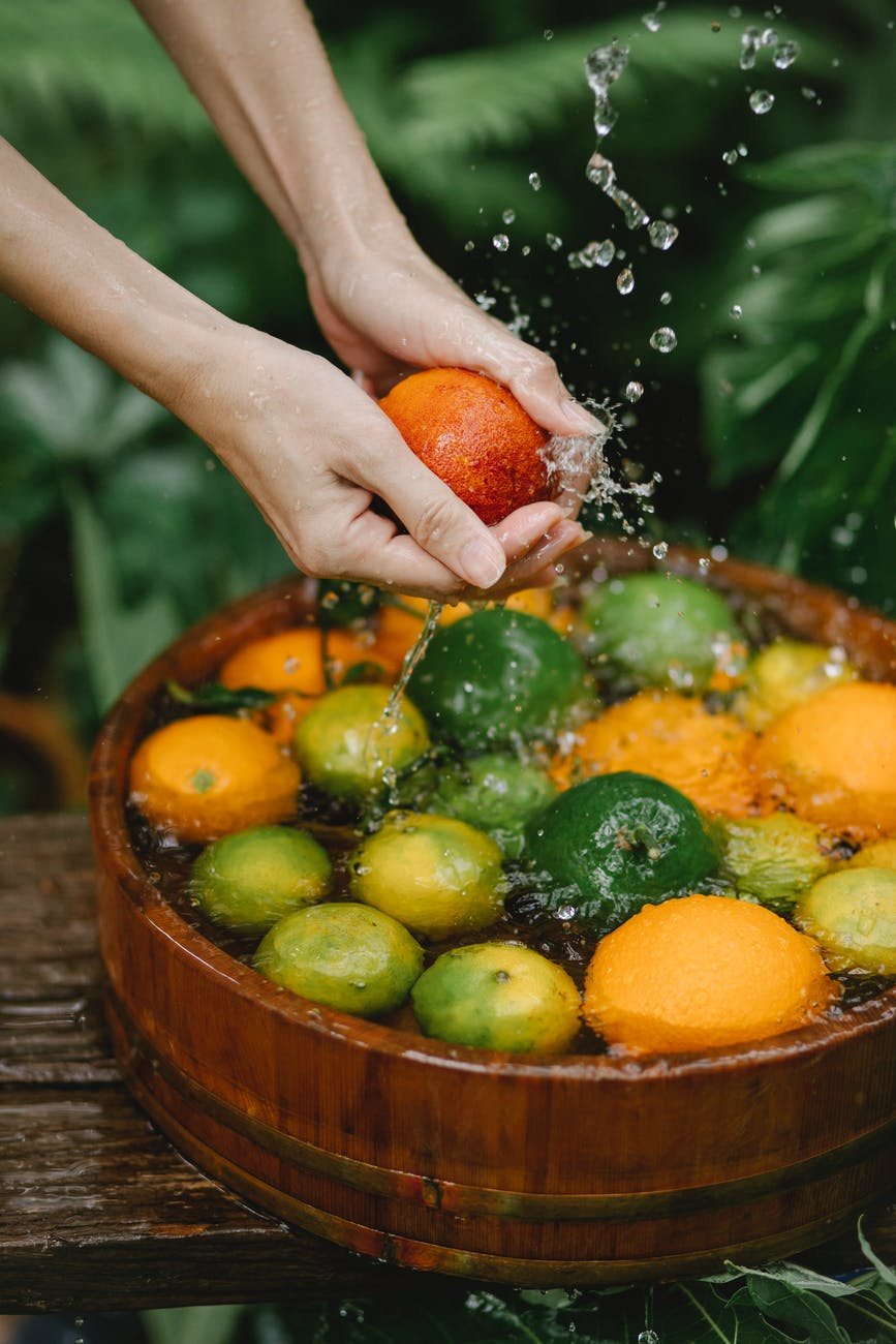 unrecognizable female gardener washing citruses in wooden container in nature