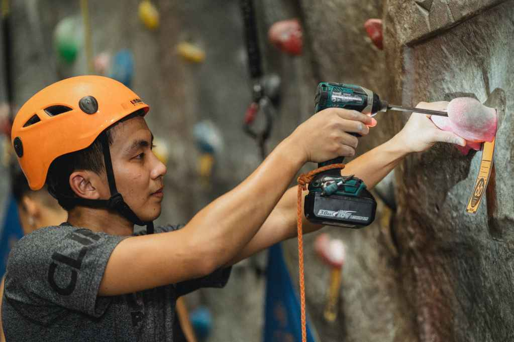 young asian specialist drilling pink climbing hold on wall in gym
