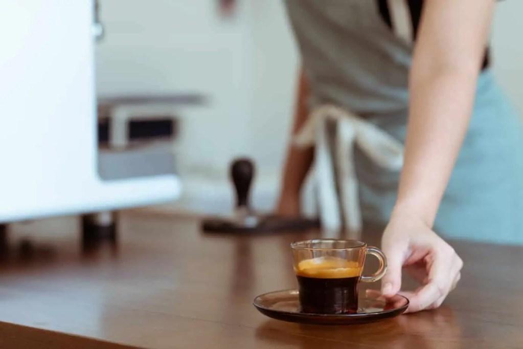 crop coffee house worker serving cup of freshly brewed espresso