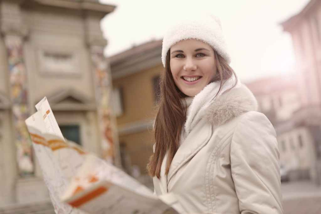happy young woman with map smiling in street