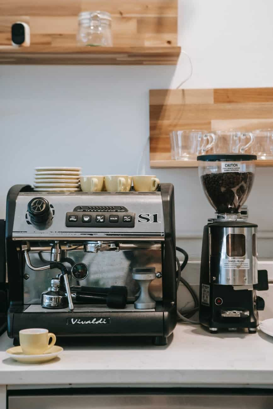coffee machine and ceramic cups in kitchen