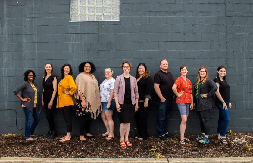Team Photo with 11 people standing in front of a gray wall. Anita Expert woman owned tech business in Michigan