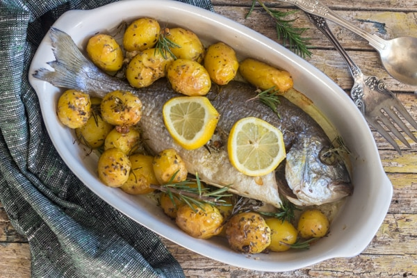 baked trout / sea bass in a white dish with small potatoes