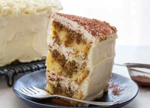 a slice of tiramisu layer cake on a black plate