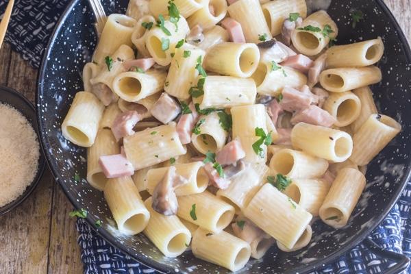 up close mushroom & ham pasta in a black pan