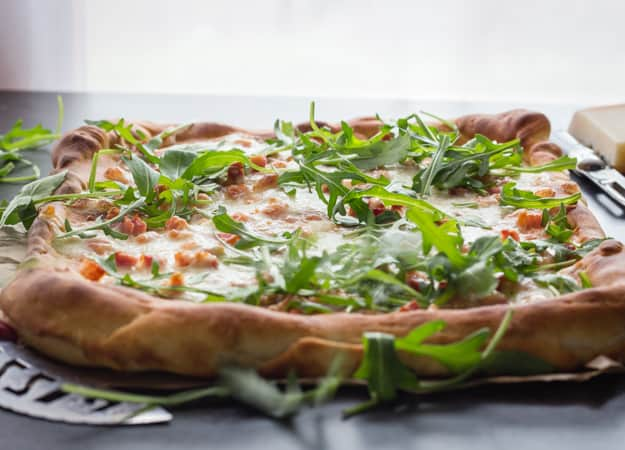 A delicious Italian Pizza Bianca (white Pizza), made with 2 cheeses, bacon (pancetta) and arugula. No sauce needed! A must try.