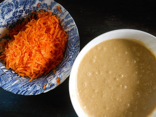 shredded carrots in a bowl and mixed cake batter in a white bowl