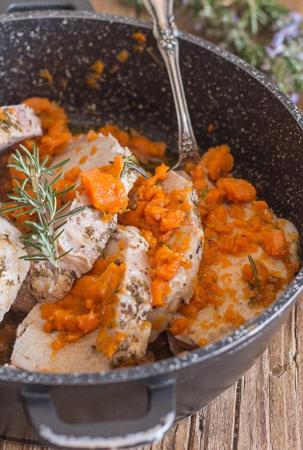 cooked roast pork loin sliced with carrots in a black pan