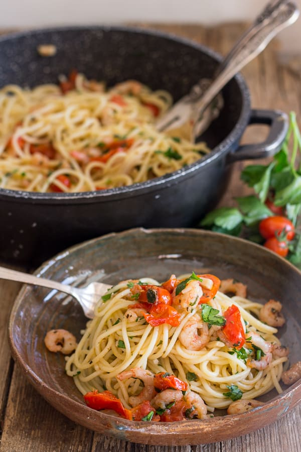 shrimp and tomato pasta in a dish and in a black pot