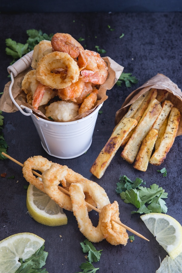 fried seafood in a small white bucket with calamari on a stick and fries in a small paper bag