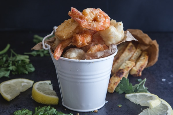 fried seafood in a white bucket with fries