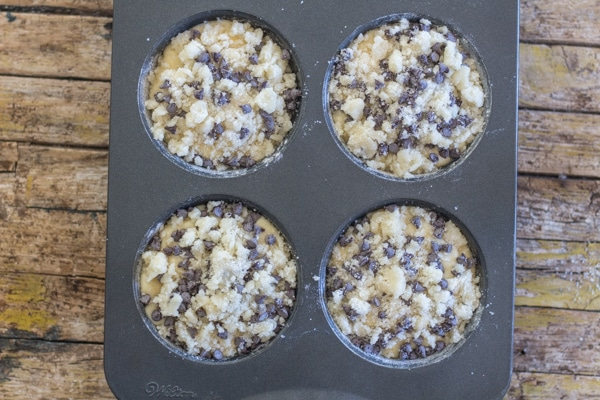 orange streusel muffins in a muffin pan ready for baking