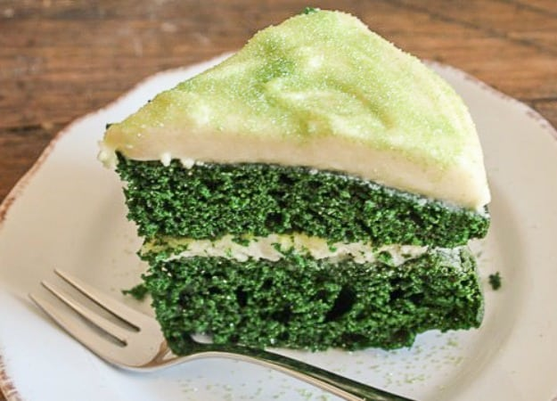 a slice of green velvet cake with baileys cream cheese frosting on a white plate