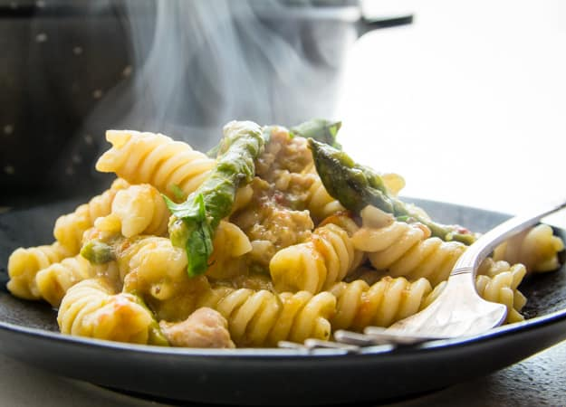 penne pasta with an asparagus cream sauce, cut up asparagus and Italian sausage grated parmesan on a black plate with a fork