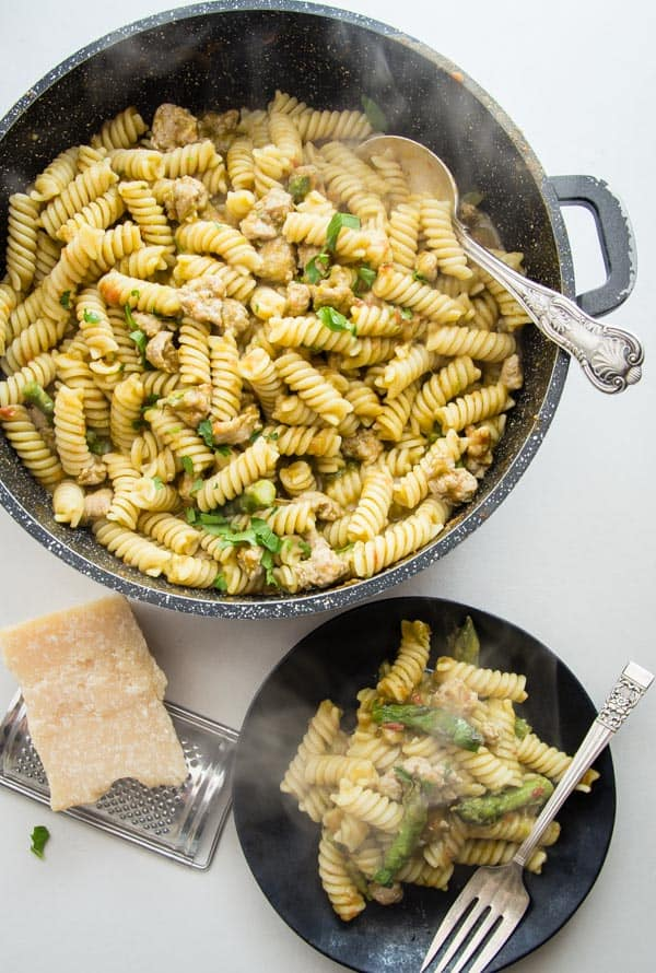 penne pasta in a asparagus cream sauce with cup up asparagus and sausage in a skillet and with some in a black plate.