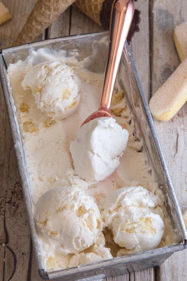tiramisu ice cream in a silver container with three scoops and a copper ice cream scoop