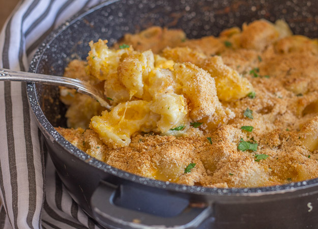baked macaroni double cheese in a skillet with a spoonful