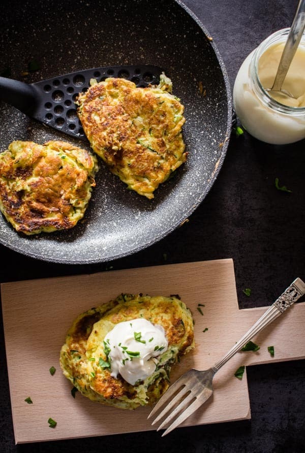 zucchini patties cooked, 2 in a pan and 1 on a wooden board with dressing on top