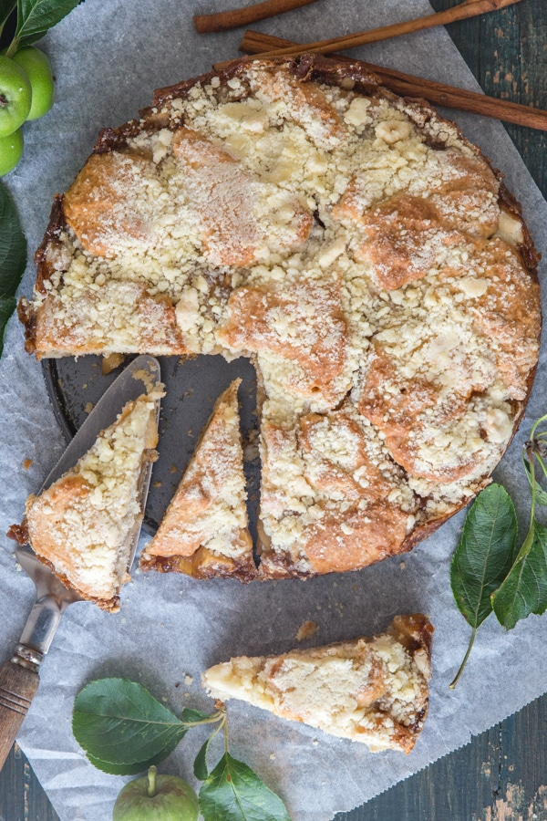 apple streusel cake with three pieces cut on white paper