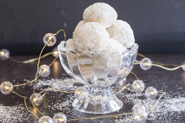 snowball cookies in a glass bowl with christmas lights on
