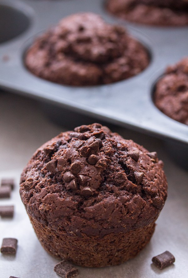 chocolate chip muffins in a large muffin tin and one in front