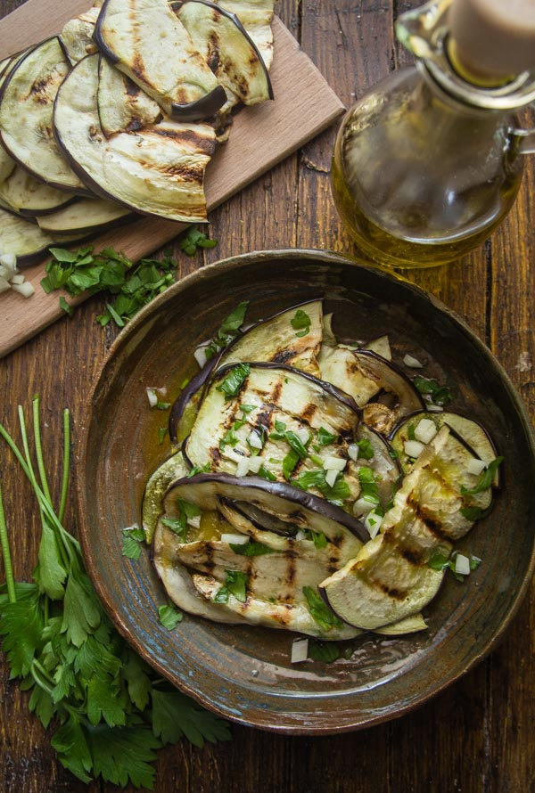 grilled eggplant tossed with parsley,garlic & oil in a brown ceramic plate