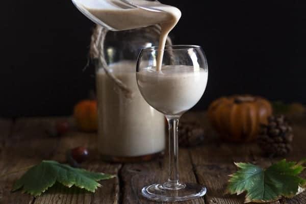 pouring pumpkin liqueur in a glass
