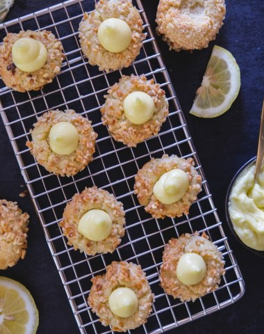 lemon thumbprint cookies on a wire rack with lemon slices