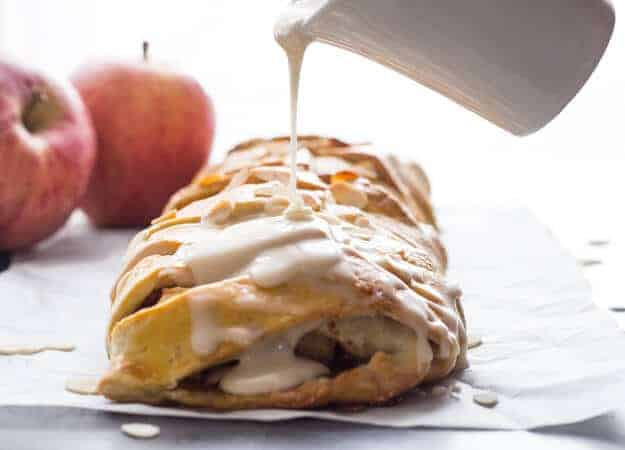 cinnamon apple strudel recipe on parchment paper with maple syrup glaze being poured from a small jar