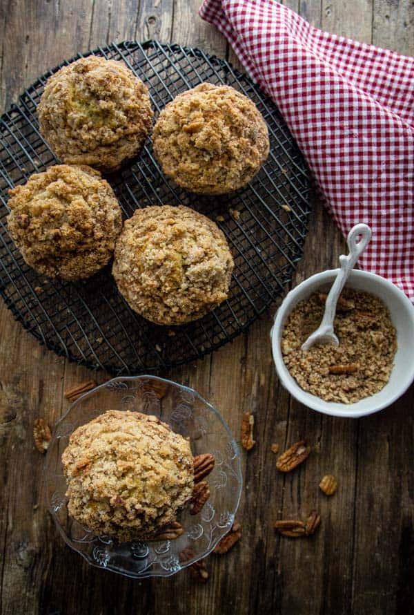 5 large pecan banana crumb muffins , 4 on a wire wrack and one on a pedestal, with ground pecans in a white bowl