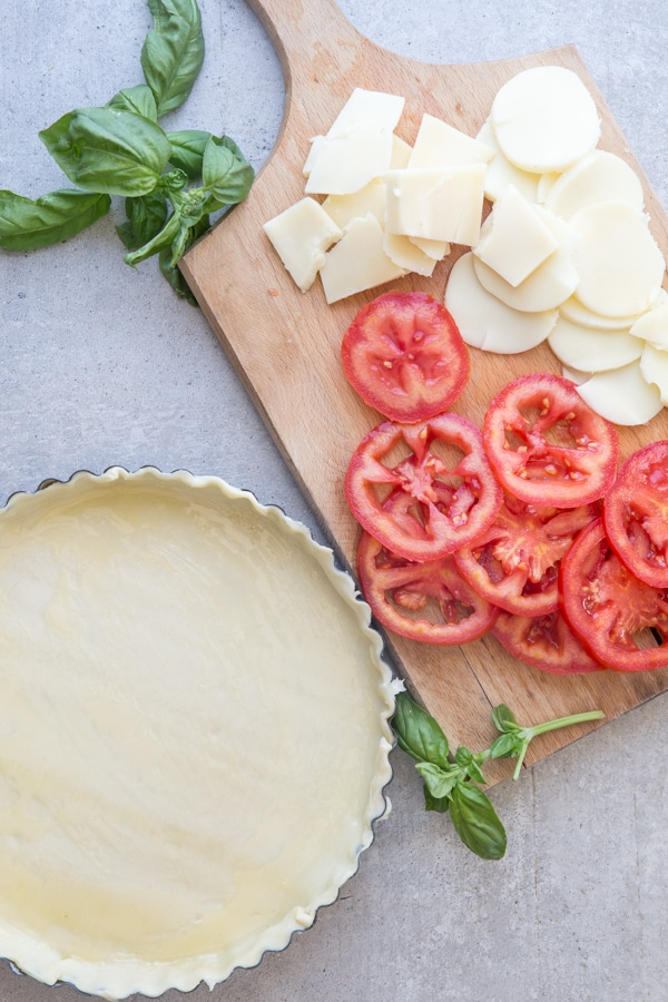 tomato pie how to make pastry dough brushed with melted butter, sliced cheese & tomatoes on a board