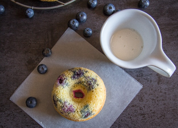 lemon glaze in a small pitcher with blueberry baked donuts and fresh blueberries