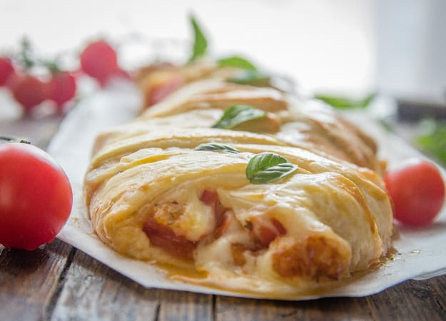 caprese strudel just baked on a wooden board