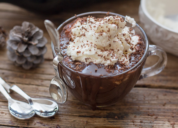 thick Italian hot chocolate in a glass mug topped with whipped cream and grated chocolate