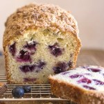 blueberry bread a cut piece on a wire rack