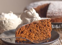 a slice of gingerbread cake and a spoonful of whipped cream on a plate with the rest of the cake in the background