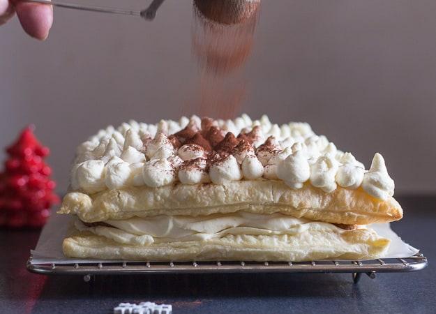 sprinkling cocoa on puff pastry tiramisu