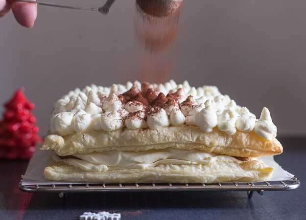sprinkling cocoa on puff pastry tiramisu