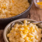 macaroni and cheese in a bowl with shredded cheddar on top