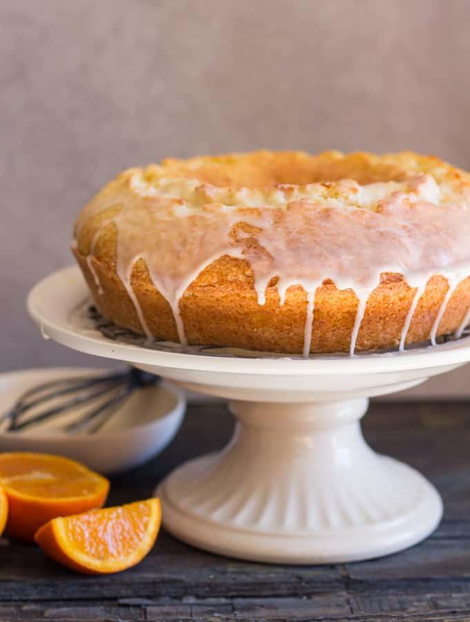 orange bundt cake on a white cake stand