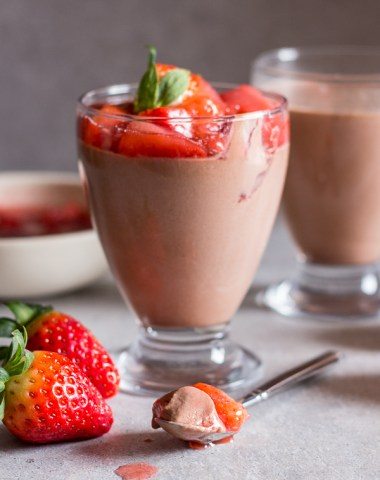 Panna cotta in a glass with fresh strawberry topping on top