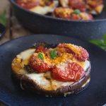 eggplant parmesan stack on a black plate