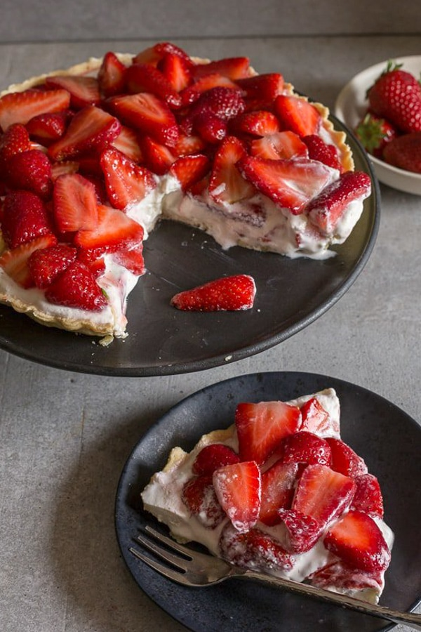 fresh strawberry pie with a slice on a black plate